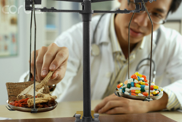 Man Weighing Pills in a Laboratory --- Image by © Simon Marcus/Corbis